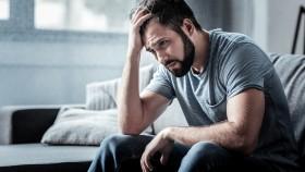 Miniatura de hombre mirando preocupado, estresado, sentado en el sofá