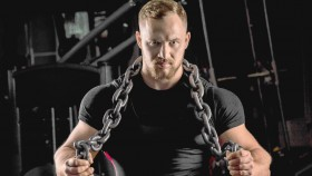 Muscular-Male-Holding-Chain-Around-Neck-and-Shoulder-Gym. thumbnail