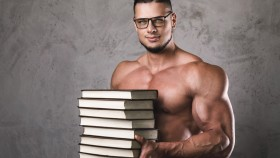 Muscular-Man-Wearing-Glasses-Holding-Stack-of-Books thumbnail