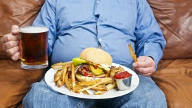 Overweight man eating junk food thumbnail