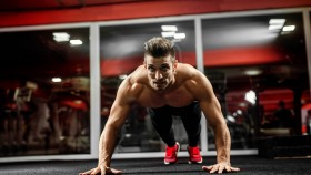 Man Performing Pushups At Gym thumbnail