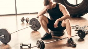Tired-Man-Surrounded-By-Weights thumbnail