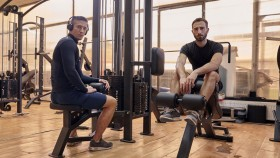 Two-Guys-Posing-In-Gym-Sitting-On-Machines thumbnail