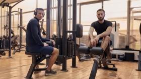 Miniatura de dos chicos posando en el gimnasio sentados en máquinas miniatura