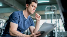 Young-Muscular-Man-Reading-Paper-Notes-In-Gym. thumbnail