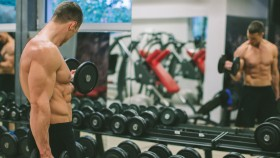 Fit Young Man Excersising With Dumb Bells At Gym thumbnail