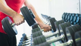 Man Picking Up Dumbbell Off Rack thumbnail