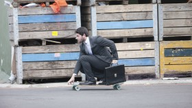 man skateboarding to work in suit thumbnail