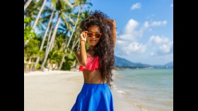 Young woman on beach wearing sunglasses thumbnail