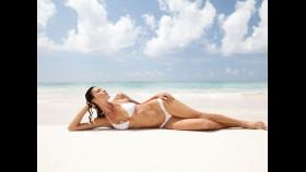 Woman posing in white bikini on beach thumbnail
