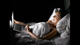 Woman on computer in bed thumbnail
