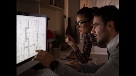 Young, attractive couple working late in office thumbnail