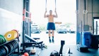 Man doing ring pullups in CrossFit-style gym